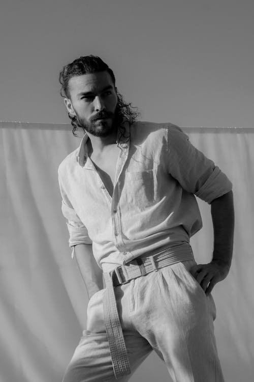 Black and white of thoughtful pensive male in stylish trousers with belt looking away