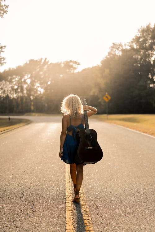 Anonymous woman with guitar walking on empty road at sunset