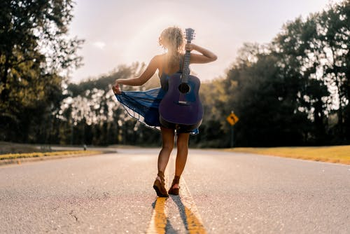 Back view full length of anonymous happy young lady with acoustic guitar in hand in stylish dress walking on empty asphalt road amidst green trees on summer sunny day