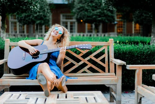 Relaxed young lady playing guitar on bench in garden