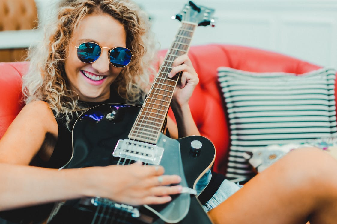 Trendy young woman playing electric guitar on leather sofa and smiling
