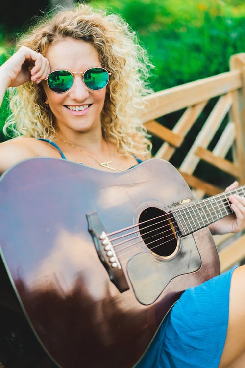 Stylish young lady with guitar recreating in green garden
