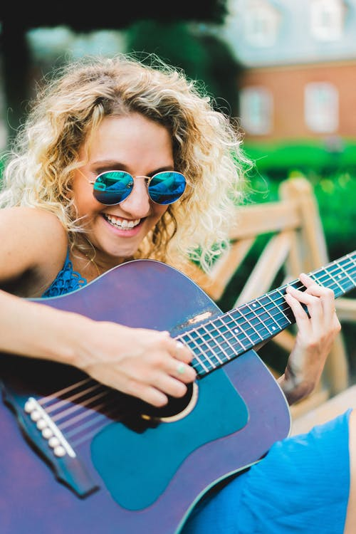 Expressive young blondie playing guitar in park