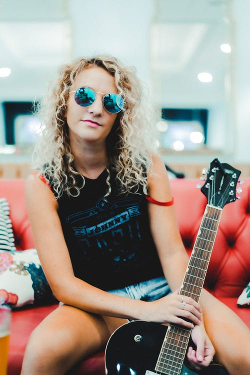 Cool young female musician with electric guitar resting on couch