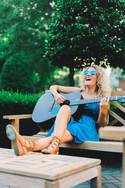 Stylish young woman chilling in park and playing guitar on bench