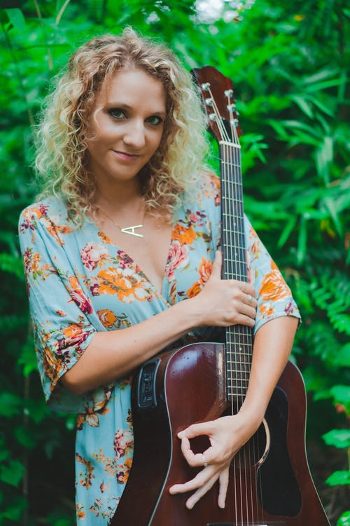 Stylish woman holding guitar and showing okay sign in forest