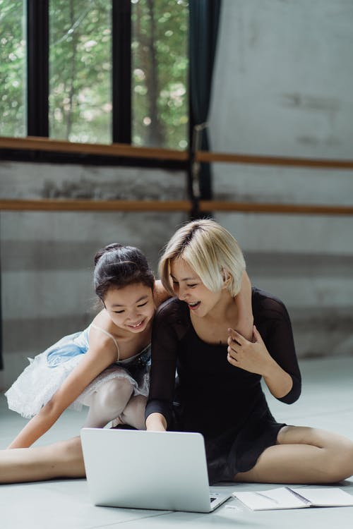 Happy Asian woman with girl in ballet studio with laptop