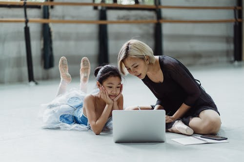 Asian girl with personal instructor using laptop in ballet studio