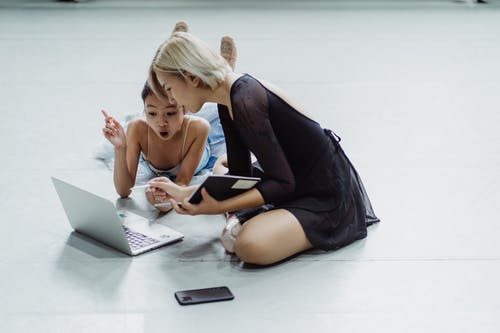 Impressed Asian little ballerina with instructor using laptop