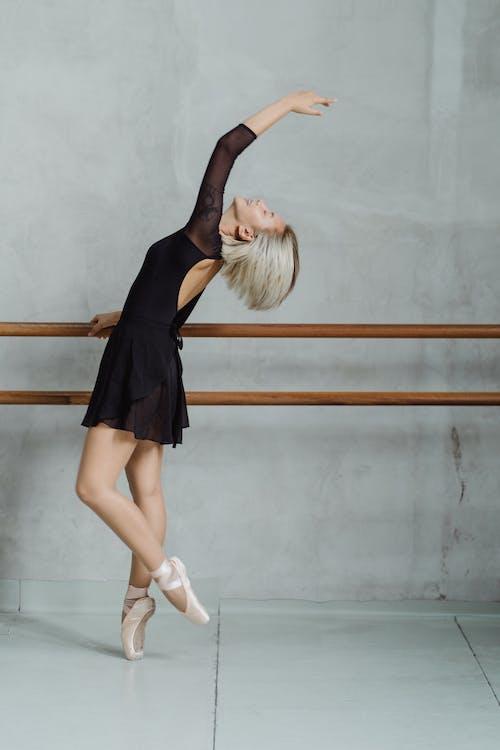 Elegante Bailarina étnica De Puntillas Y Sosteniendo La Barra