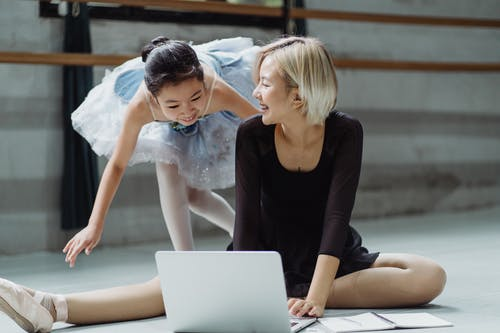 Cheerful ethnic girl and dance coach laughing while using laptop