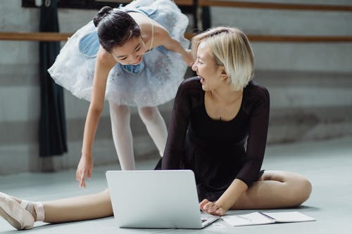 Cheerful ethnic girl in tutu with trainer surfing laptop