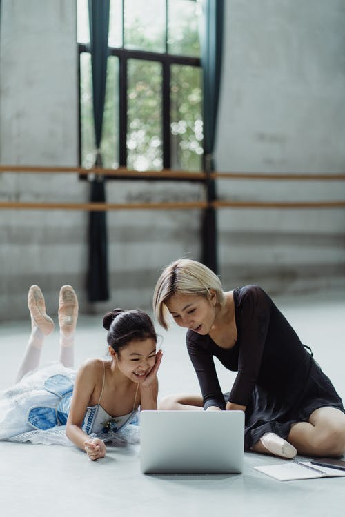 Laughing ethnic ballerina with personal instructor browsing laptop
