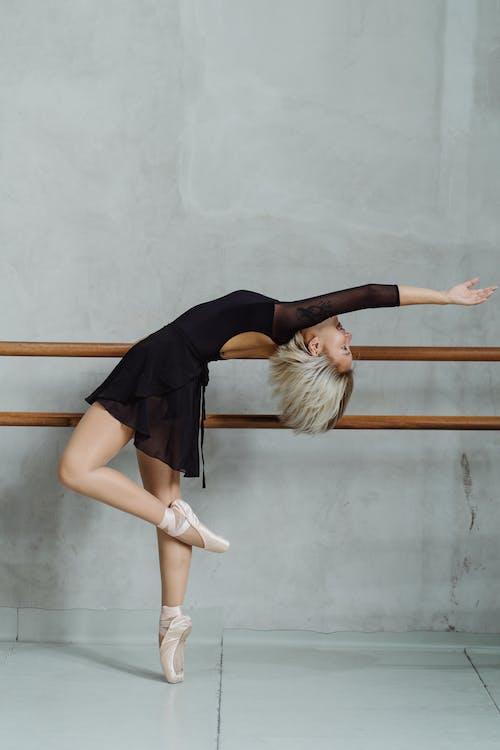 舒展身体的年轻种族跳芭蕾舞者在有纬向条花的演播室