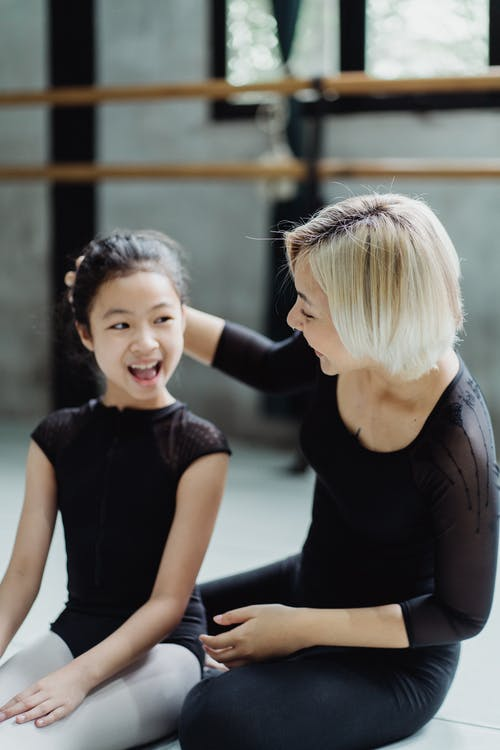 Cheerful little Asian ballerina with instructor resting on floor in studio