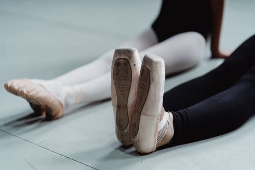 Anonymous female dancers in pointes stretching legs on floor in studio
