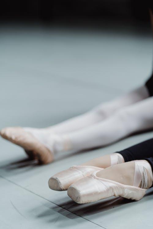 Crop ballerinas stretching feet during training in daylight