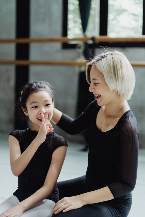 Cheerful young and little ethnic ballerinas sitting on floor and laughing