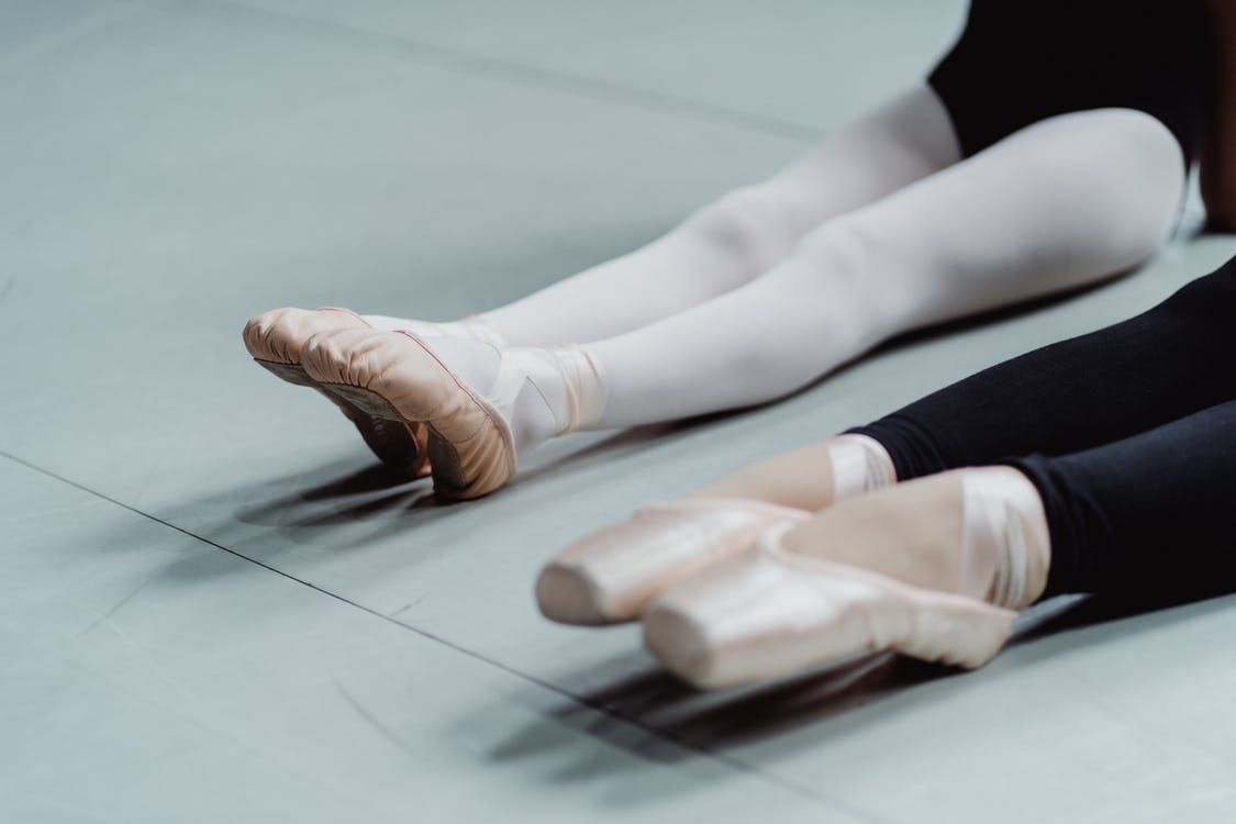 From above of crop anonymous woman and girl in pointes warming up on floor before ballet training in light studio