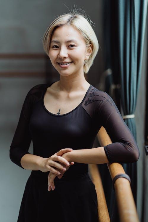 Smiling young ethnic ballerina relaxing in dance studio