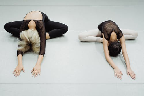 From above of unrecognizable young flexible ballerinas doing stretching exercise in Butterfly pose during dance class