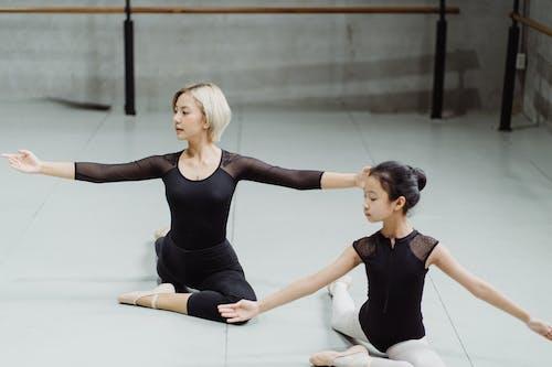 Flexible ethnic ballerinas exercising on floor in studio