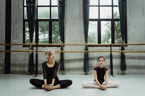 Full body of concentrated Asian little girl with female ballet teacher sitting on floor in Butterfly pose and stretching hips during training