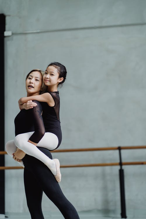 Cheerful girl in leotard and ballet instructor dancing together in studio with barre