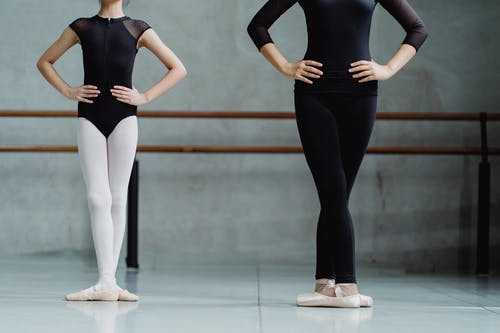 Crop unrecognizable ballerinas standing in third position