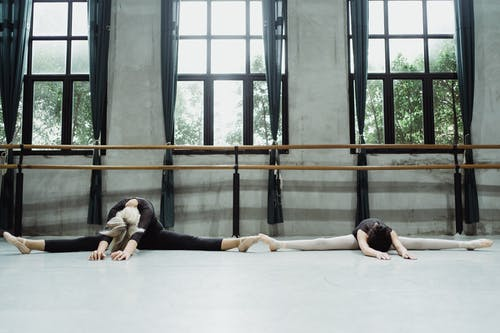 Full length anonymous woman and teenage ballerinas in leotards doing splits on floor and stretching bodies in ballet studio