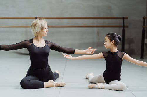 Young Asian female ballet instructor and ballerina girl in leotard performing Pigeon Pose and outstretching arms gracefully in contemporary studio
