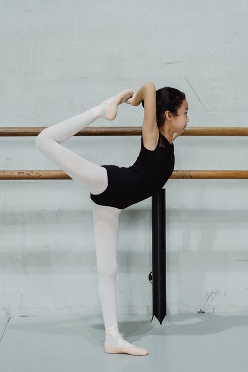 Side view full length slim girl ballerina in leotard standing near barre and raising leg behind back gracefully while attending ballet class in studio