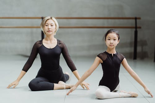 Asian ballerina woman and girl performing Pigeon Pose in studio