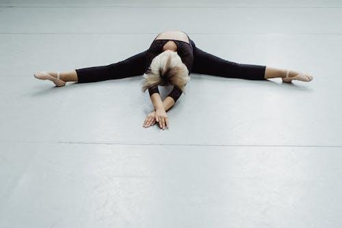 Full length anonymous fit ballerina in leotard doing split and bending body forward in light ballet studio
