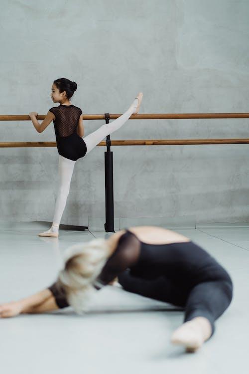 Ballerina girls stretching legs in studio