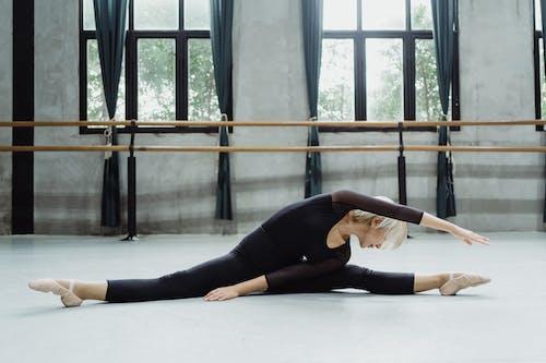 Full length slim flexible ballerina in black leotard doing split and stretching body to left while practicing in modern ballet school