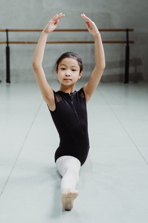 Full body of small Asian girl doing twine with hands above head on floor in ballet studio