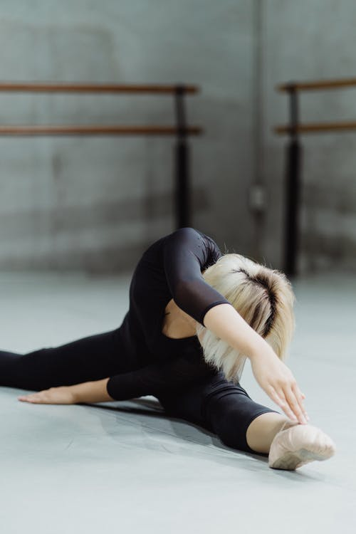 Flexible faceless ballerina doing twine and bending to leg of floor during rehearsal in ballet class