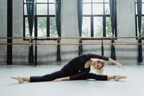 Full body of flexible ballet dancer bending to leg while stretching legs in classroom