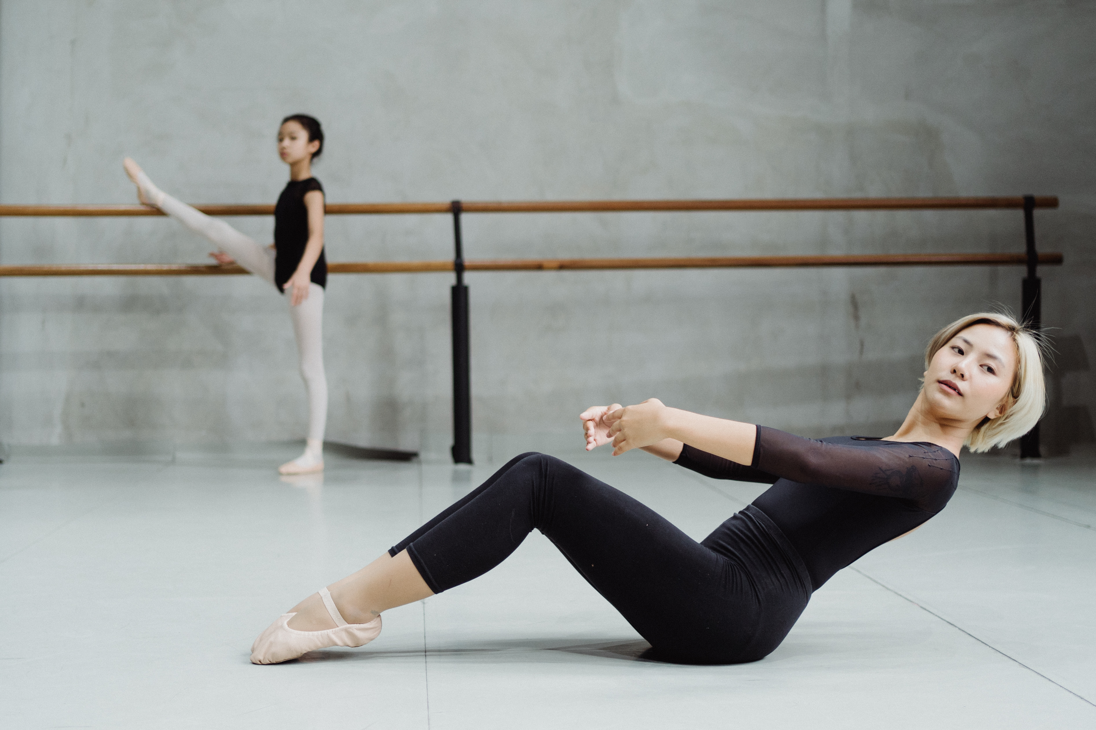 focused ethnic woman practicing in dance studio with pupil