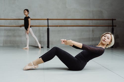 Side view full body of Asian ballet instructor rehearsing with girl in dance class