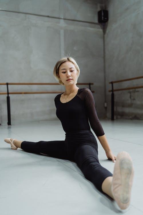 Full body of focused Asian female ballet dancer doing split while leaning on hands on floor