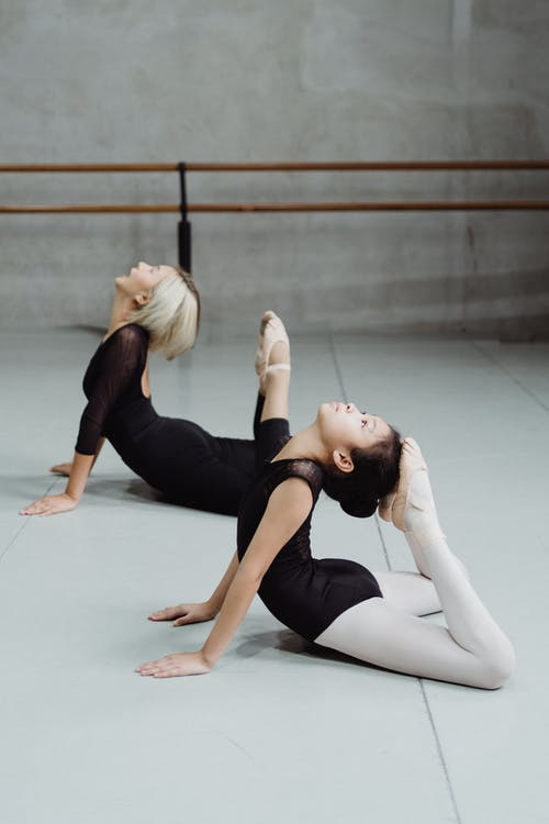 Flexible Asian ballerinas doing Cobra position in dance studio