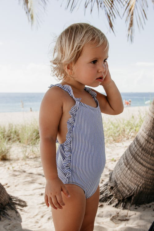 Charming little girl with short blond hair in swimsuit touching face and standing on  sandy beach near sea in sunny day