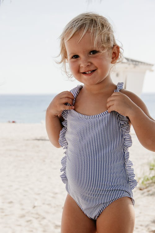 Smiling little girl with short blond hair in swimsuit standing on sandy beach near blue water in sunny day