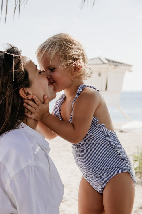 Happy little girl kissing mother on beach near sea