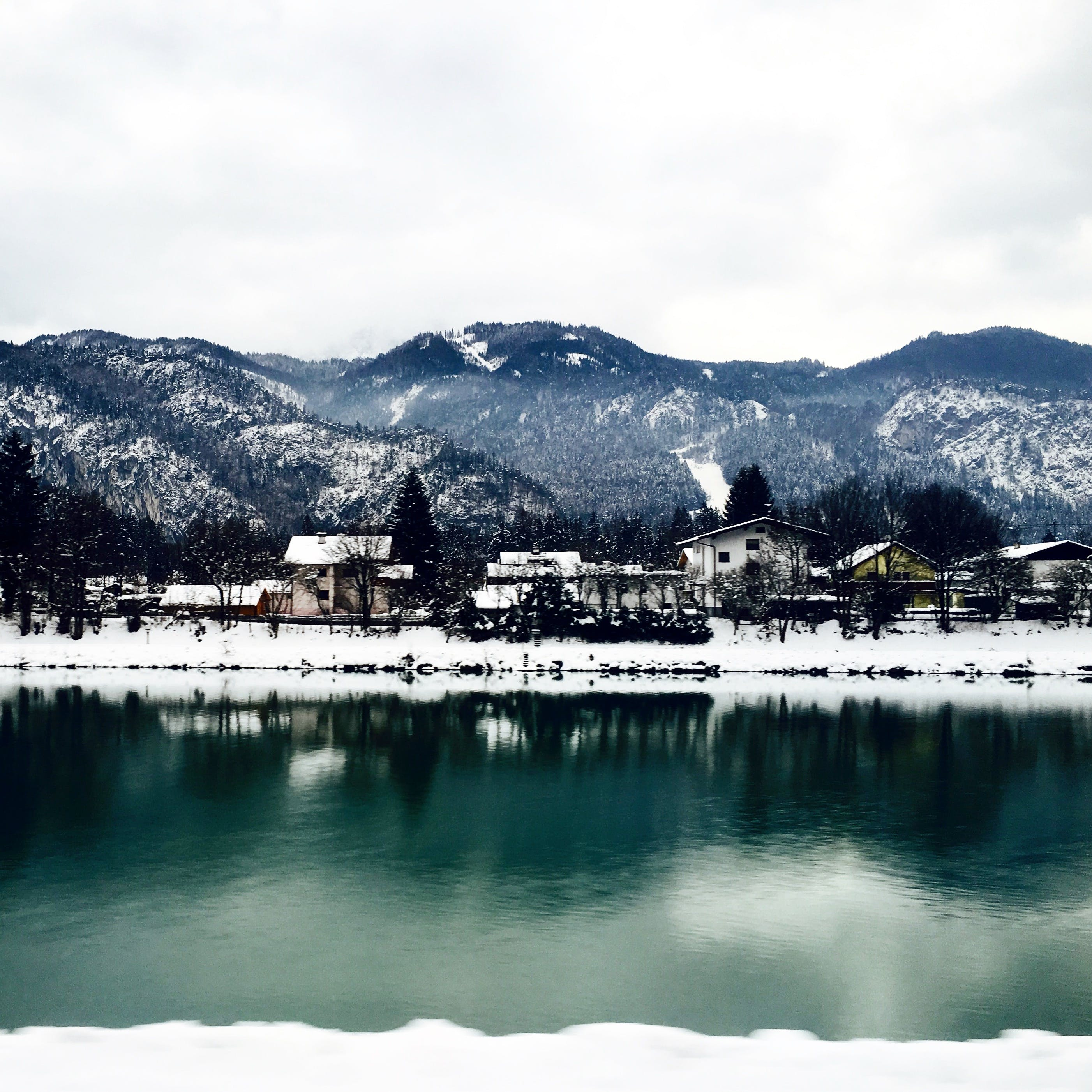 White Houses in Front of Mountains Under White Cloudy Sky