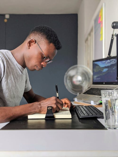 Man Taking Notes at Desk