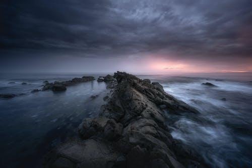 Overcast sky above boulders in sea in evening