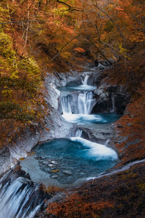 Turquoise cascade in autumn forest